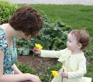 Mary offering her mommy a daffodil